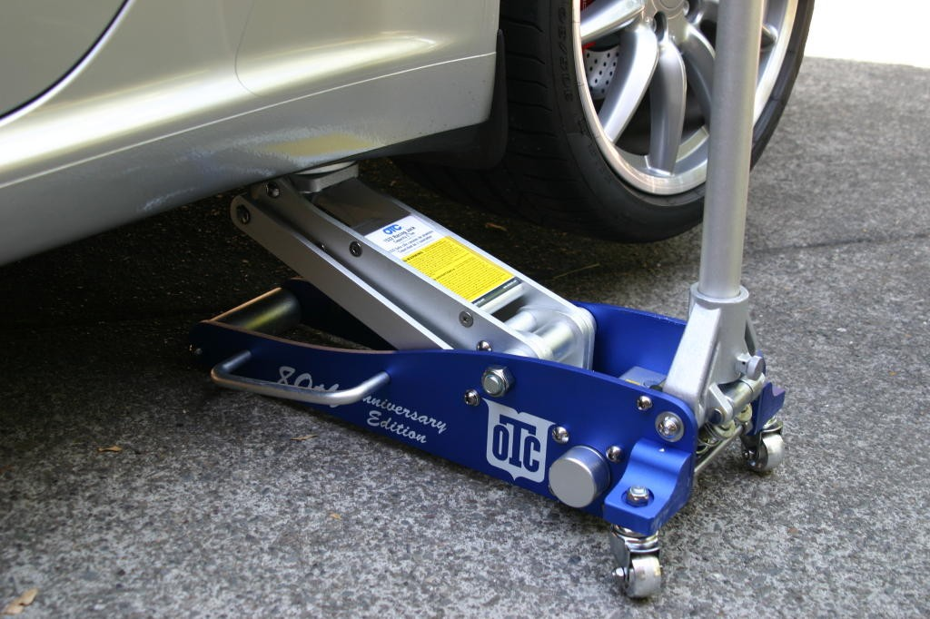 using a floor jack to lift a vehicle